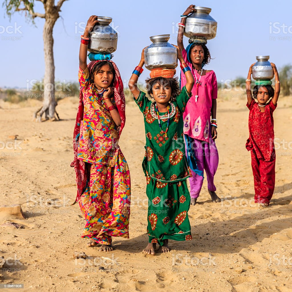 Indian little girls carrying on their heads water from well stock photo