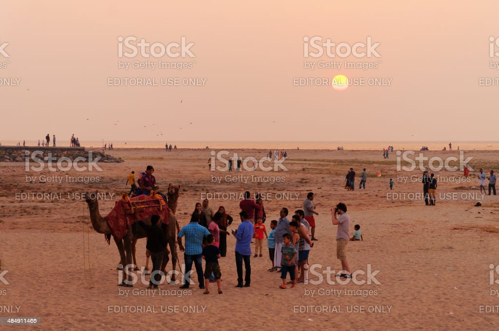 Indian local tourists with a camel on the beach stock photo