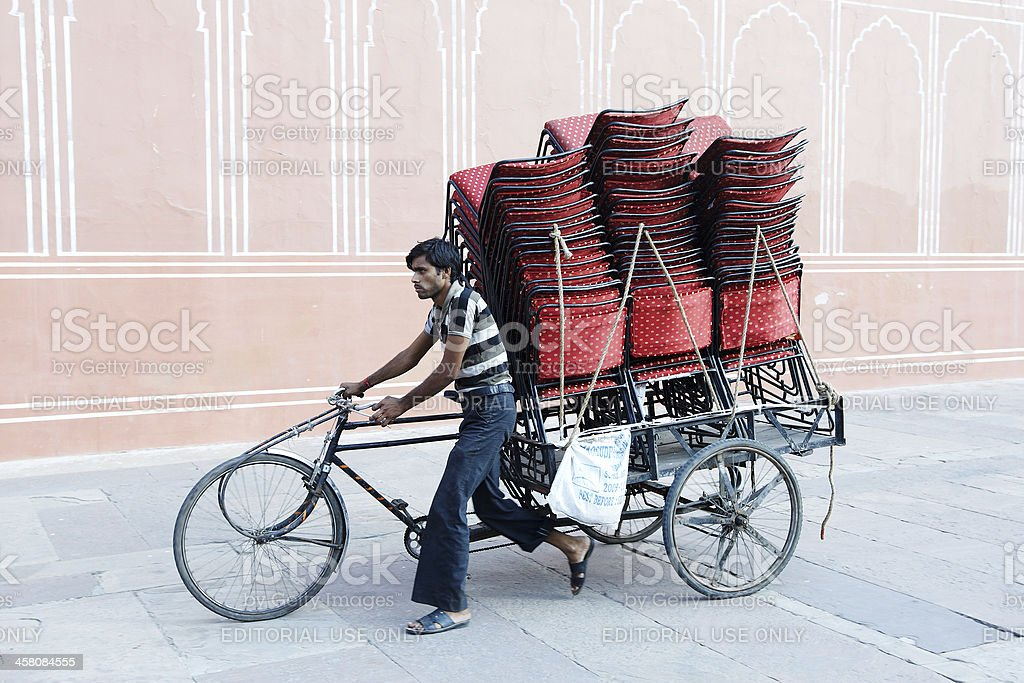 Indian man carrying chairs on his cycle rickshaw stock photo