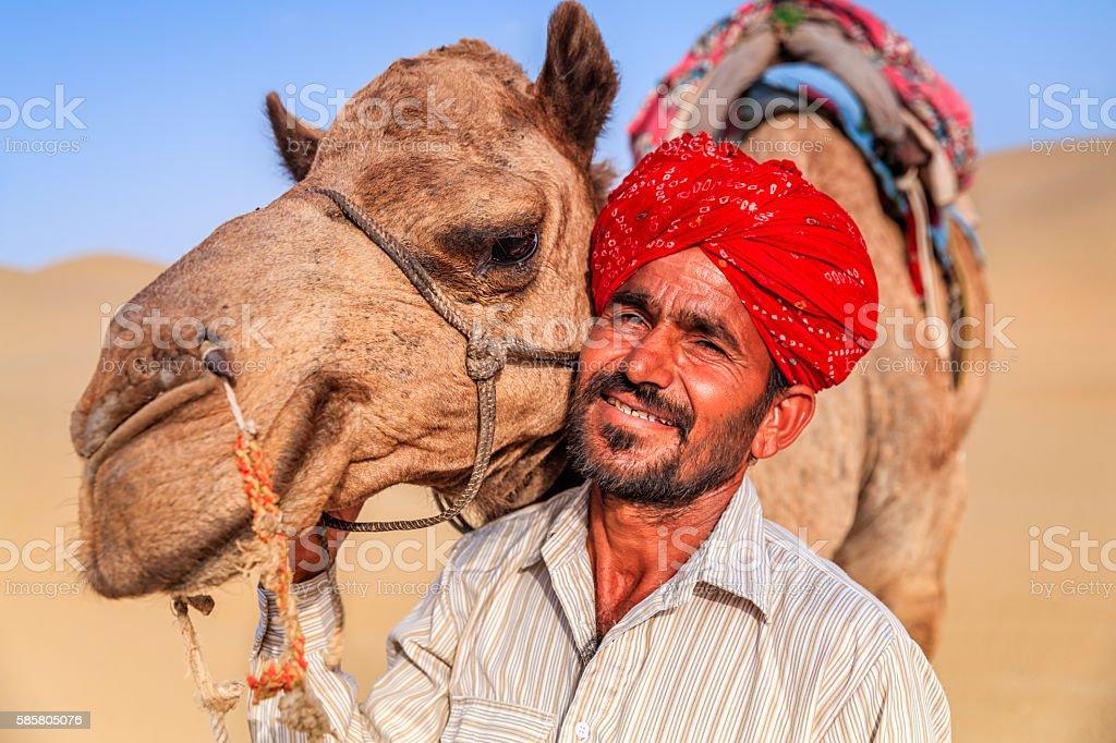 Indian man holding camel on sand dunes, Rajasthan, India stock photo