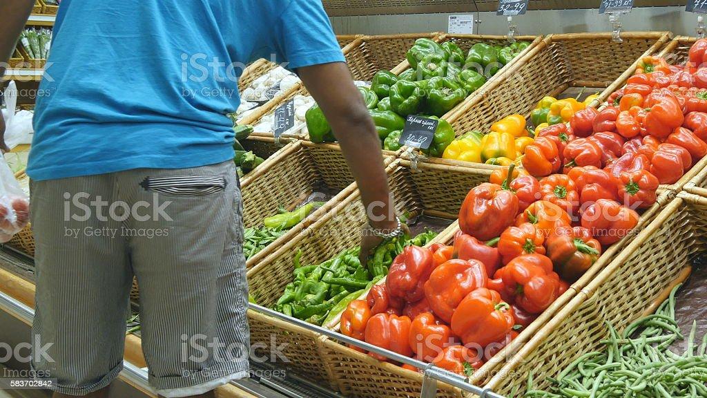 Indian man is choosing peppers in a grocery supermarket. Guy foto de stock libre de derechos