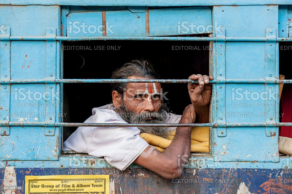 Indian man looking outside window of train stock photo