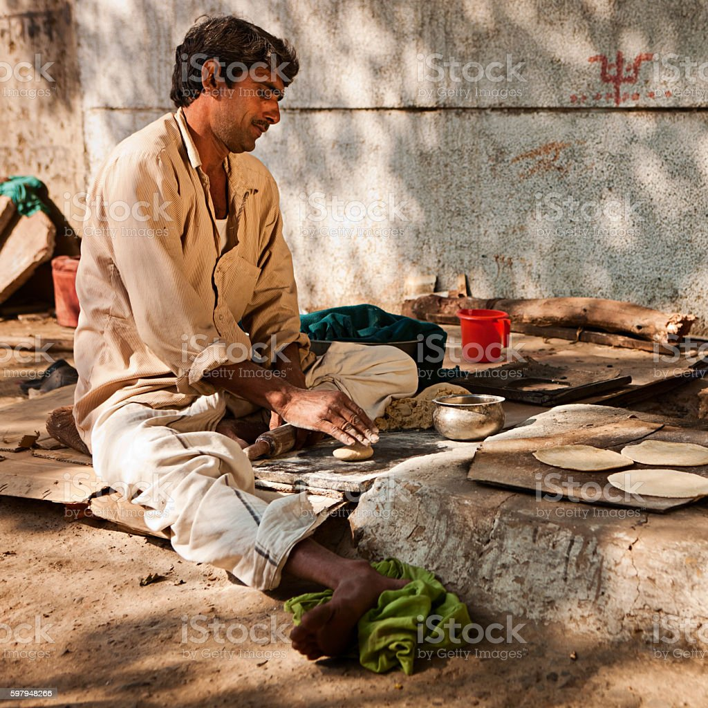Indian man preparing chapatti bread in Delhi, India stock photo
