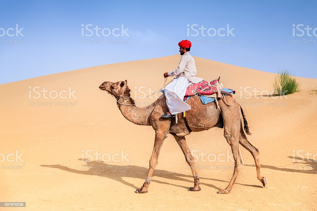 Indian man riding camel on sand dunes, Rajasthan, India stock photo