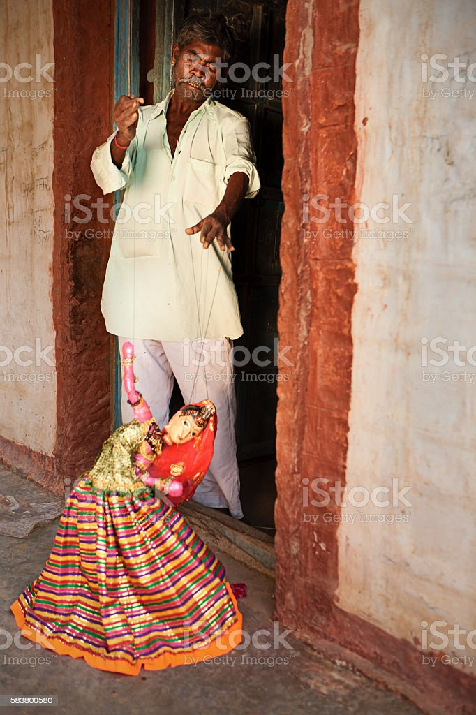 Indian man showing how to play with puppets. Rajasthan stock photo