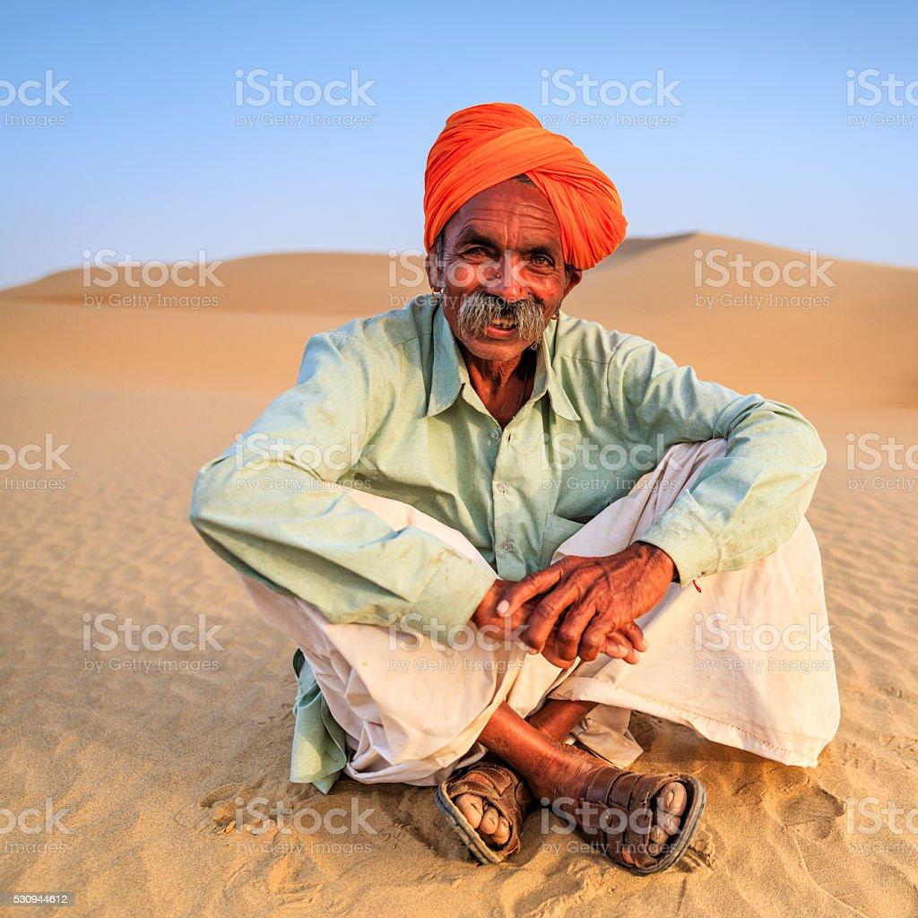 Indian man sitting on a sand dune, desert village, India stock photo