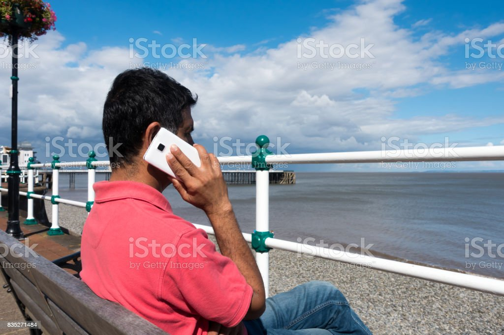 Indian Man sitting on Bench talking on Smartphone stock photo