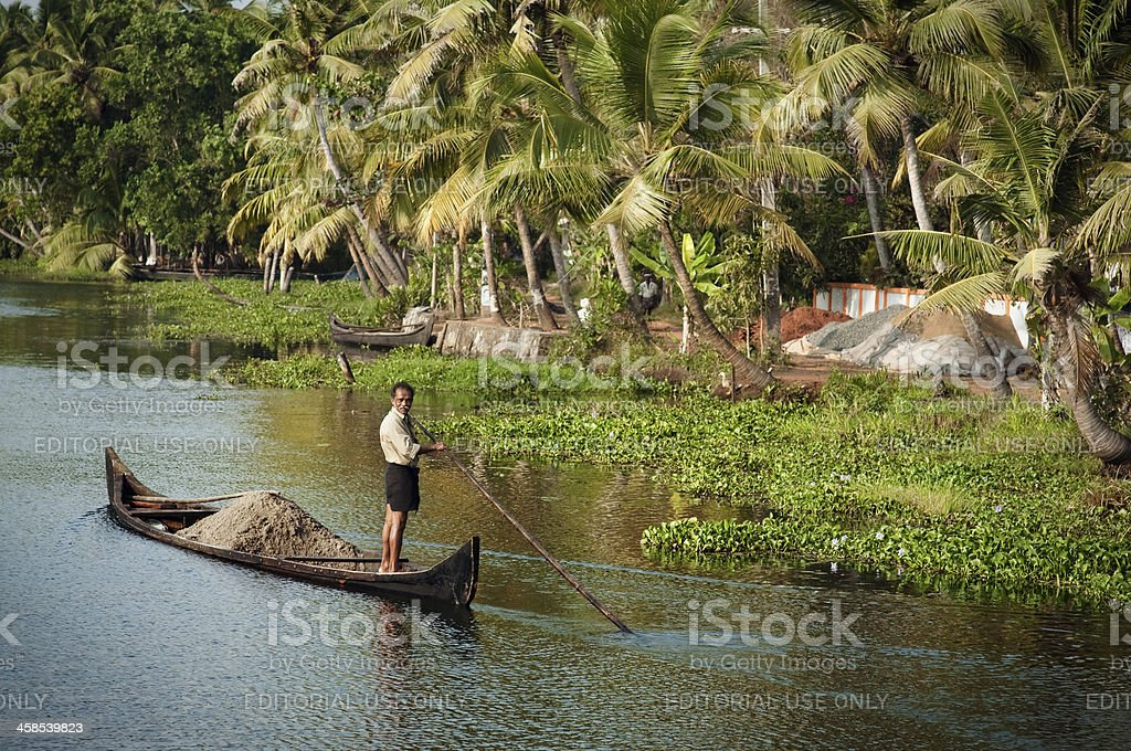 Indian man transporting soil in the boat. stock photo