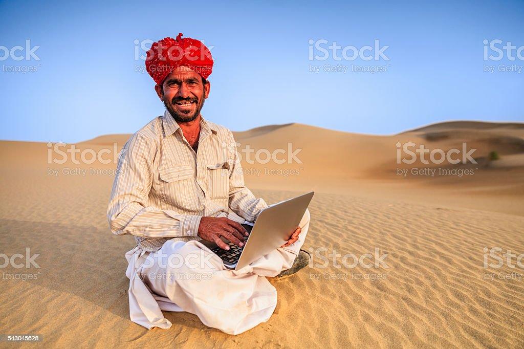 Indian man using a laptop, desert village, India stock photo