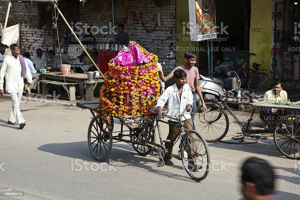 Indian man wheeling bicycle with Diwali flower arrangement on royalty-free stock photo