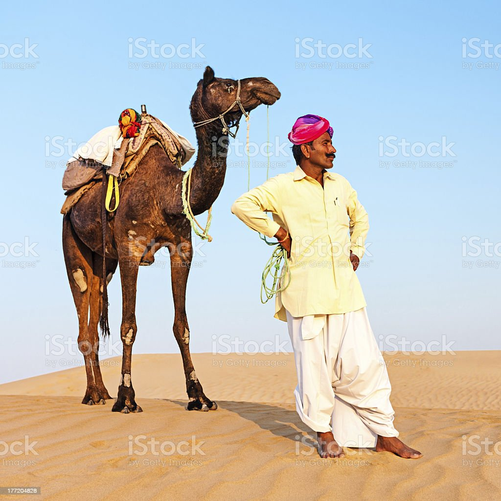 Indian man with camels during crossing sandunes royalty-free stock photo