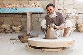 Indian man working at potter's wheel, Rajasthan, India
