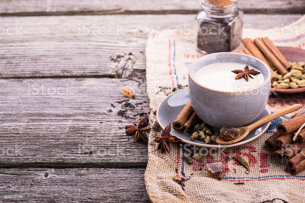 Indian masala tea with spices and milk stock photo