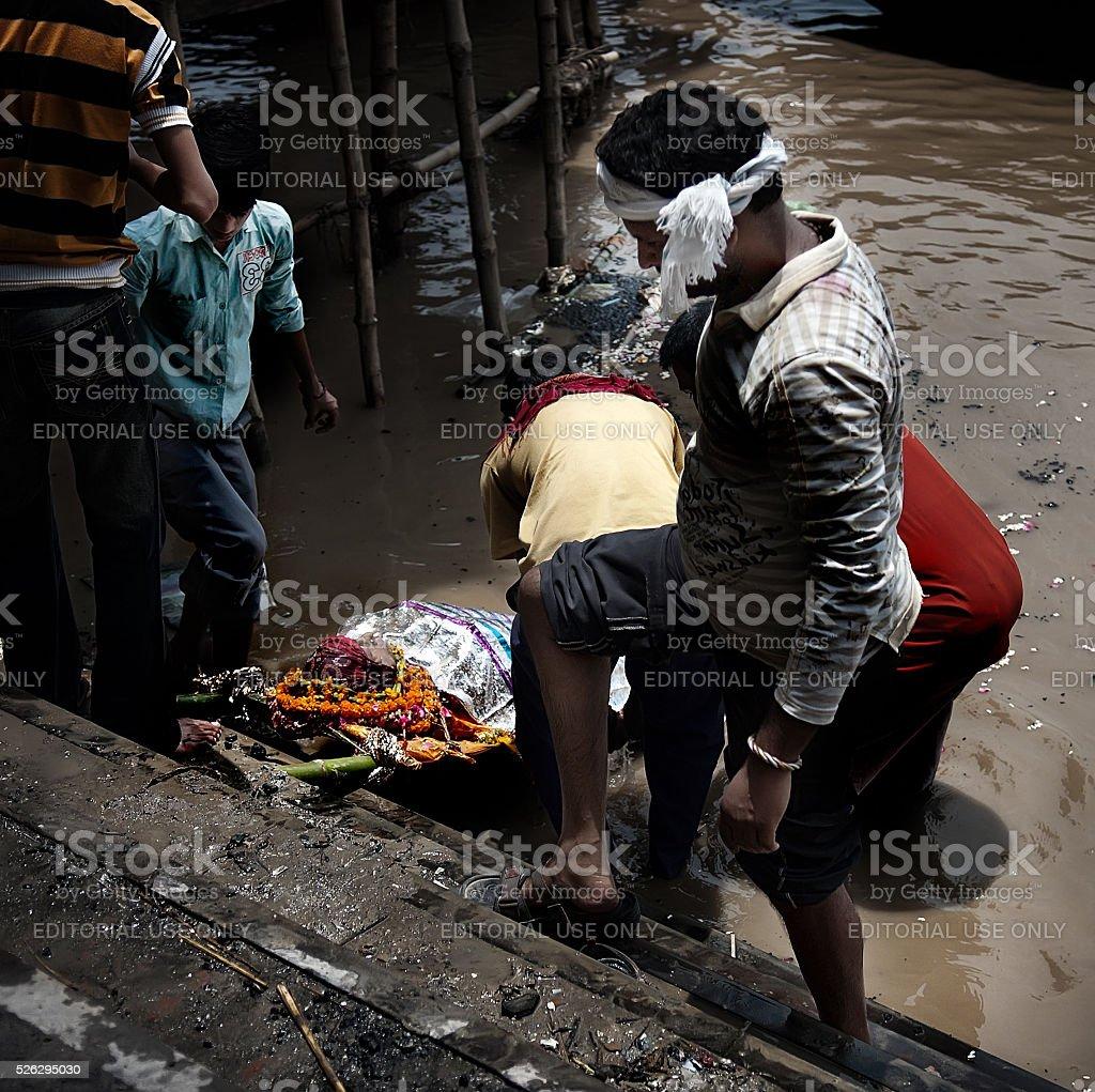 Indian men bathe deceased relative in Ganges river at Varanasi stock photo