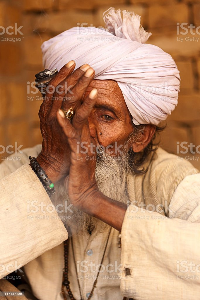 Indian old man smoking a pipe royalty-free stock photo