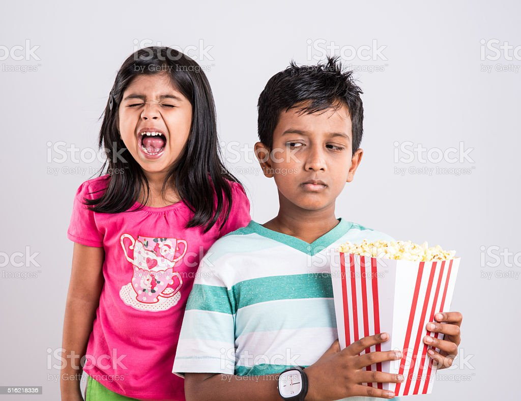 indian or asian cute and boy eating popcorn stock photo