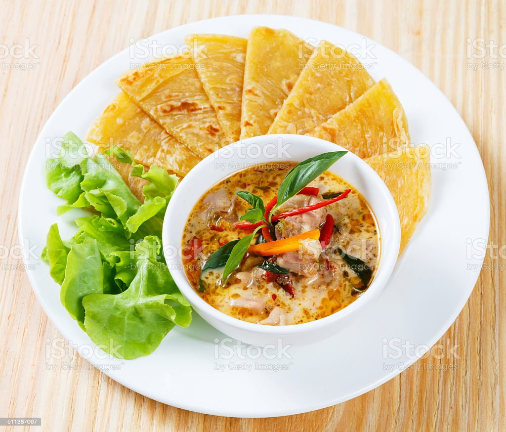 Indian pancake with chicken curry stock photo