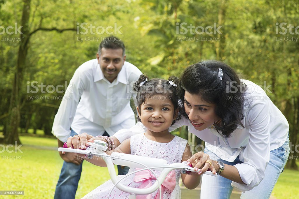 Indian  parent teaching child to ride a bike stock photo