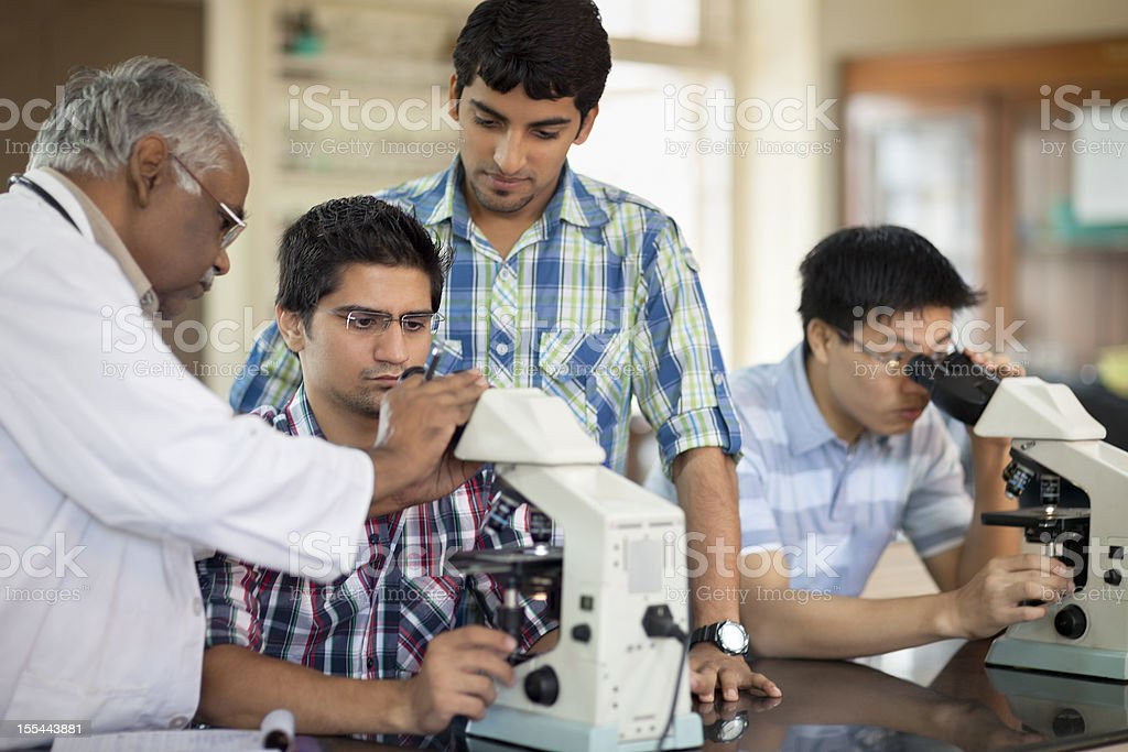 Indian Professor Teaching Students Microscopy royalty-free stock photo
