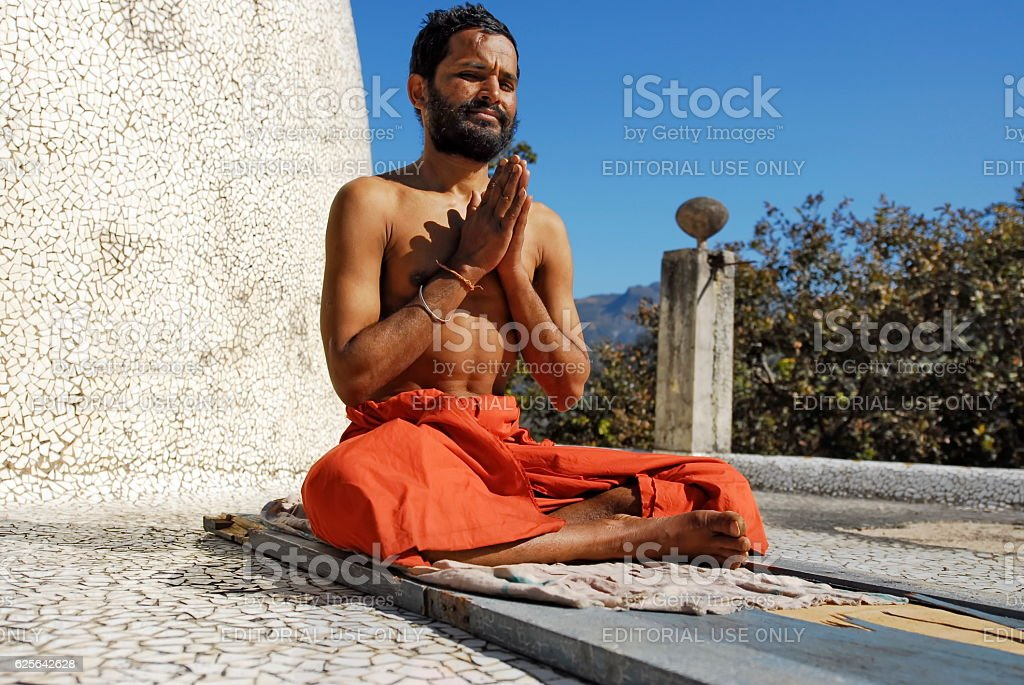 Indian sadhu does exercises of yoga, Maharishi Ashram, Rishikesh, India. stock photo