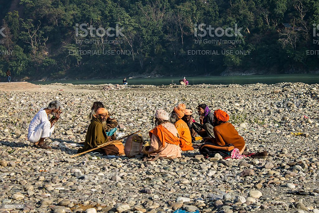 Indian sadhus siting on the beach near River Ganga stock photo