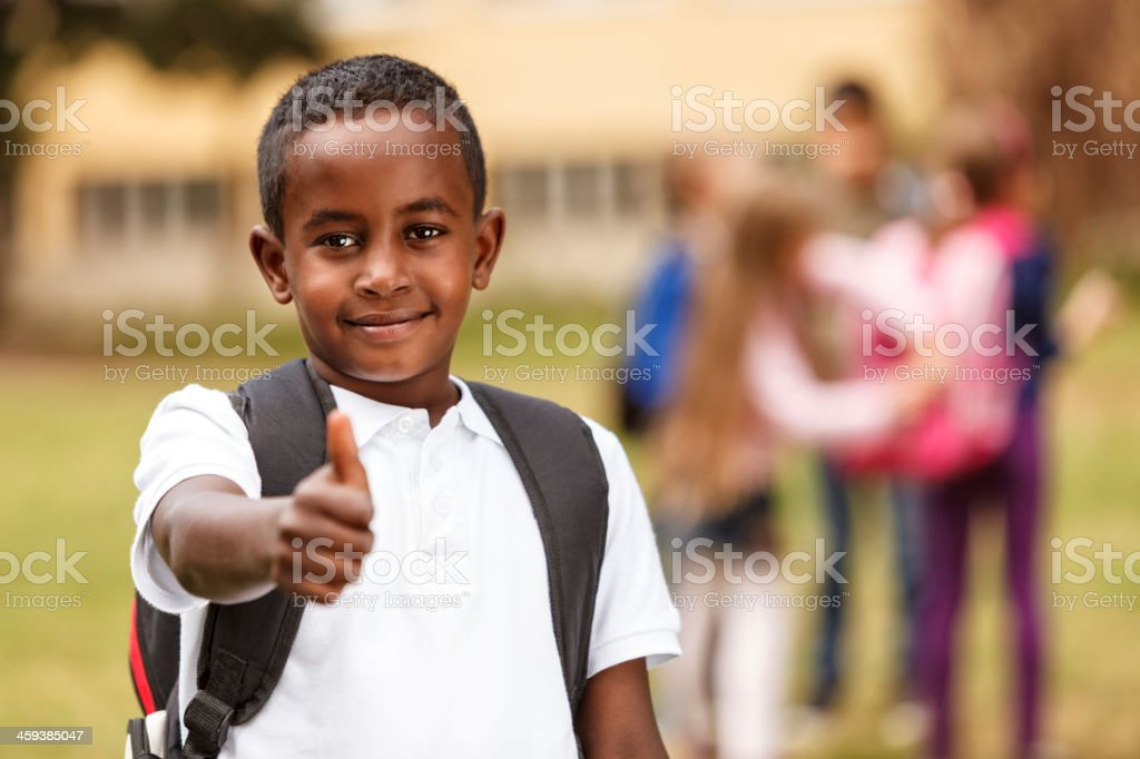 Indian schoolboy giving the thumbs up in front of a group stock photo
