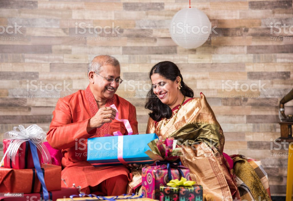 Indian senior couple in traditional wear opening gift boxes, asian couple and diwali gifts stock photo