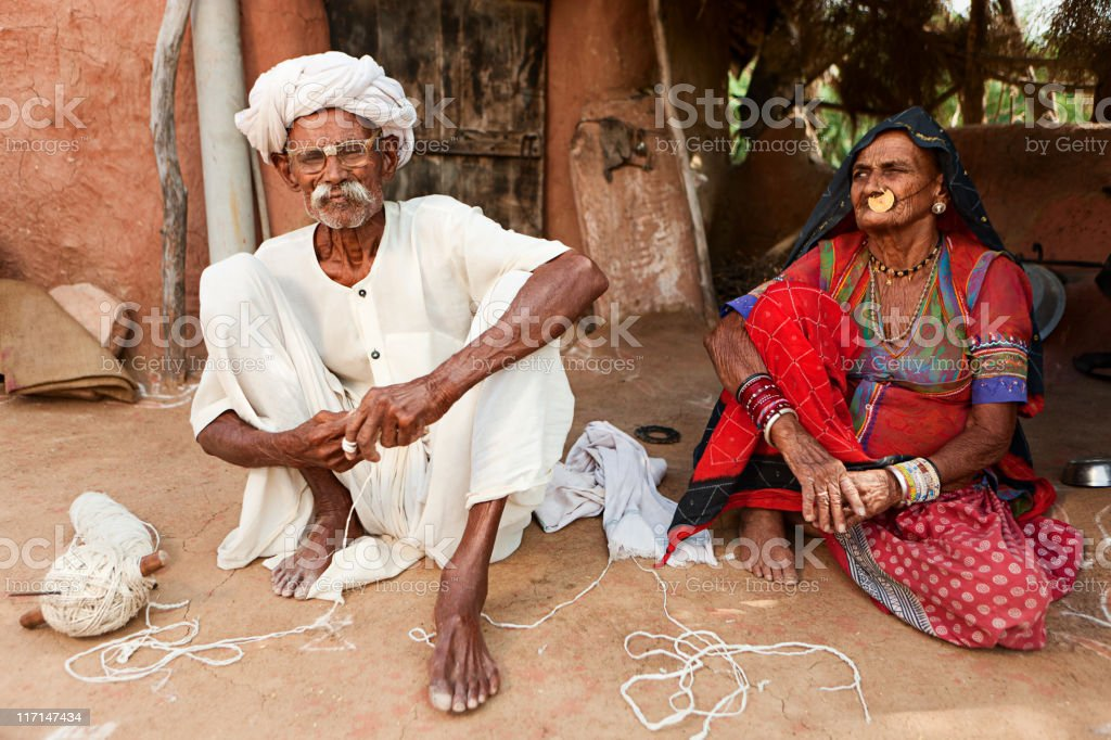 Indian senior couple sitting inside clay hut. Bishnoi village. Rajasthan. royalty-free stock photo