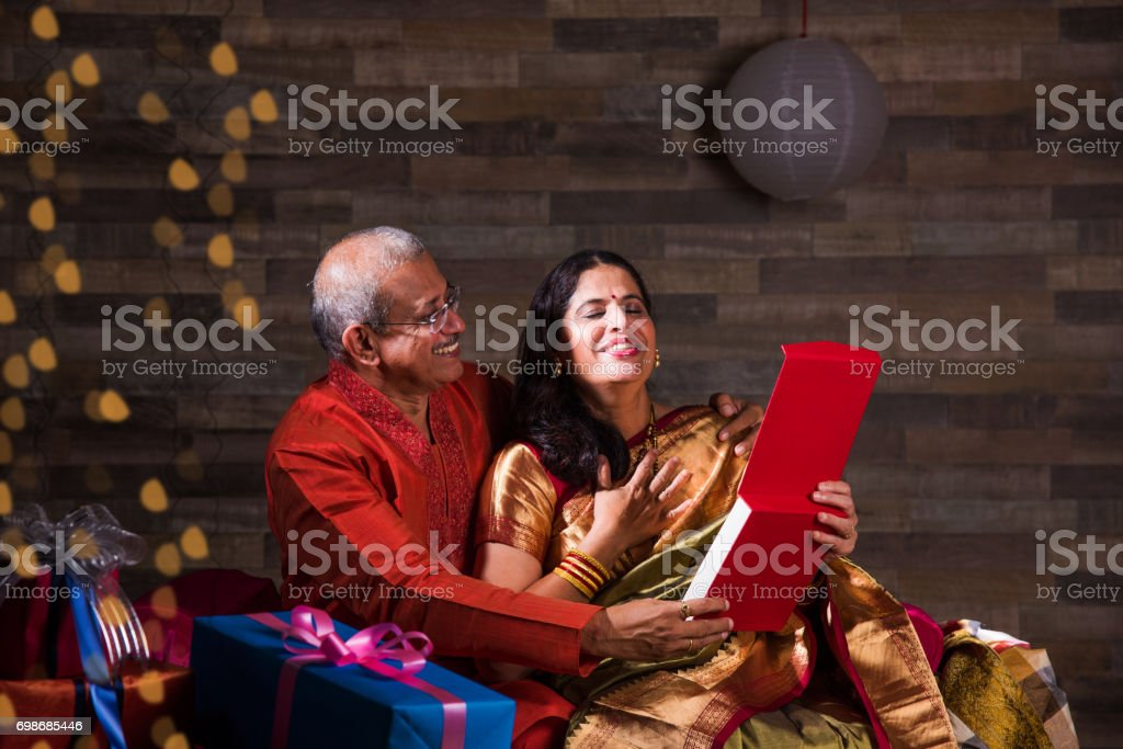 Indian senior man gifting neckless to his wife while sitting on sofa on diwali festival stock photo