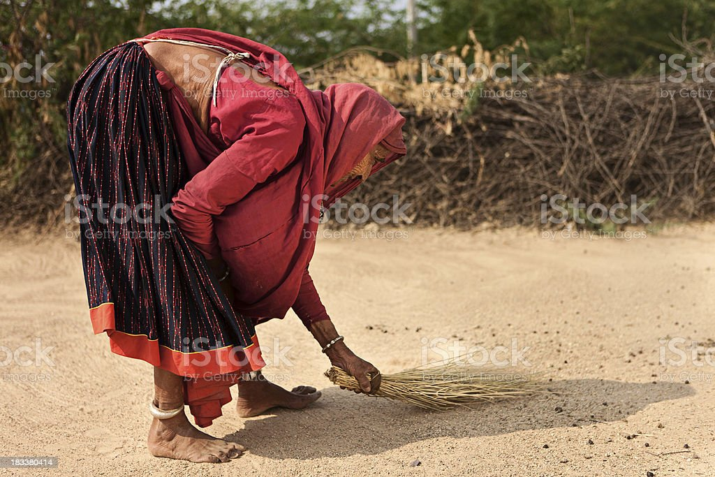 Indian senior woman sweeping the yard. Bishnoi village. Rajasthan. stock photo
