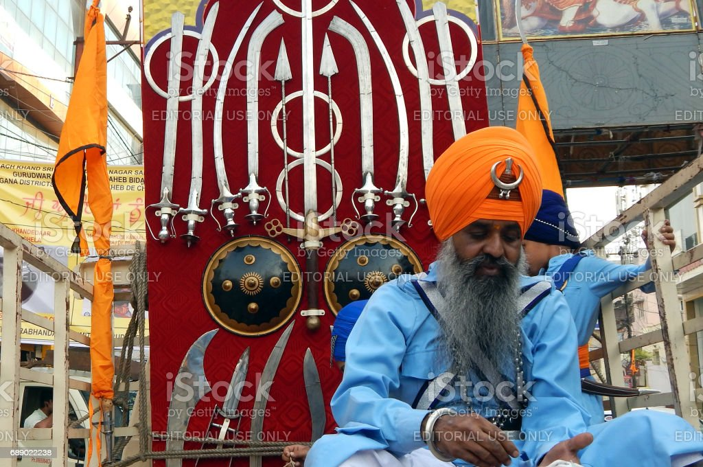 Indian sikh man wait with Weapons on truck to demonstrate combat form Gatka in Nagar kirtan on Vaisakhi festival ,Hyderabad,India stock photo