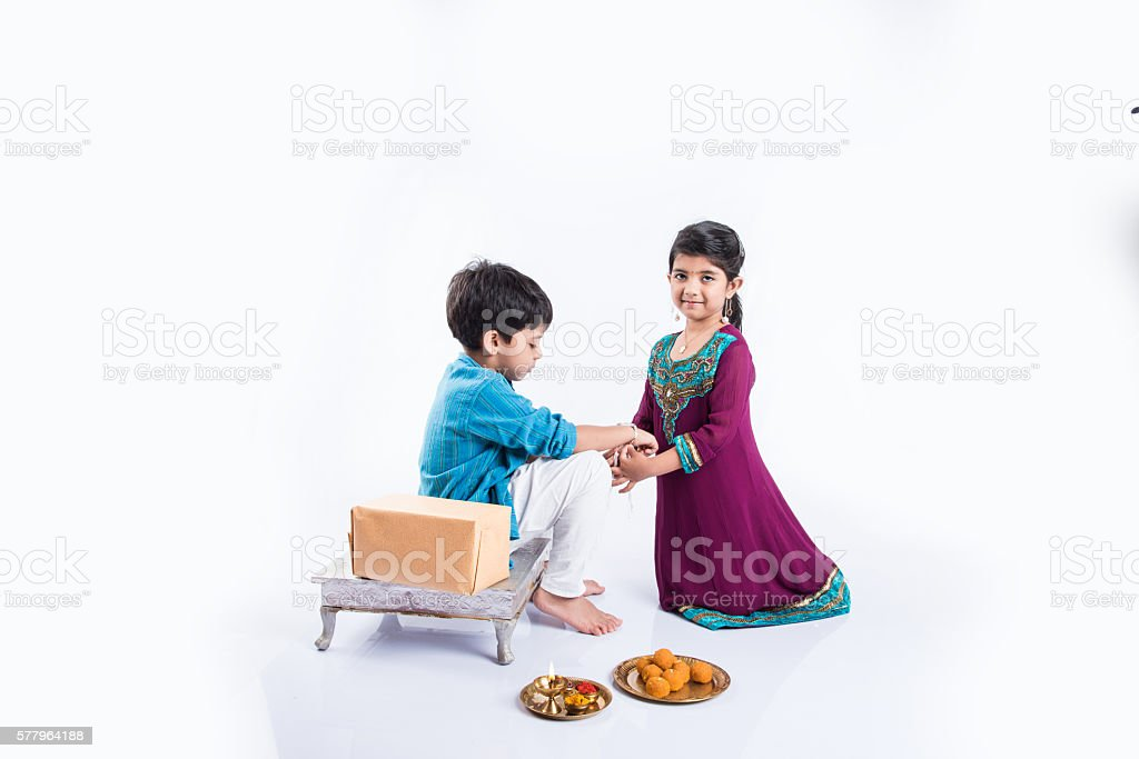 indian small girl tying rakhi to small brother on rakshabandhan stock photo