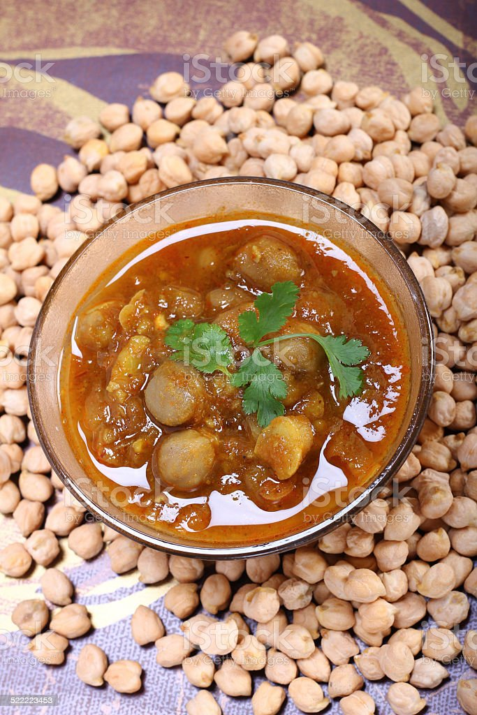 indian spicy chana masala with raw chickpeas, cardamom on top stock photo