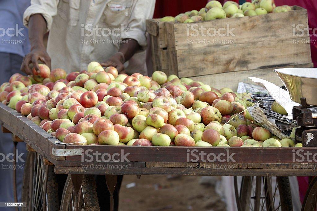 Indian street vendor pushing handcart of fresh apples royalty-free stock photo