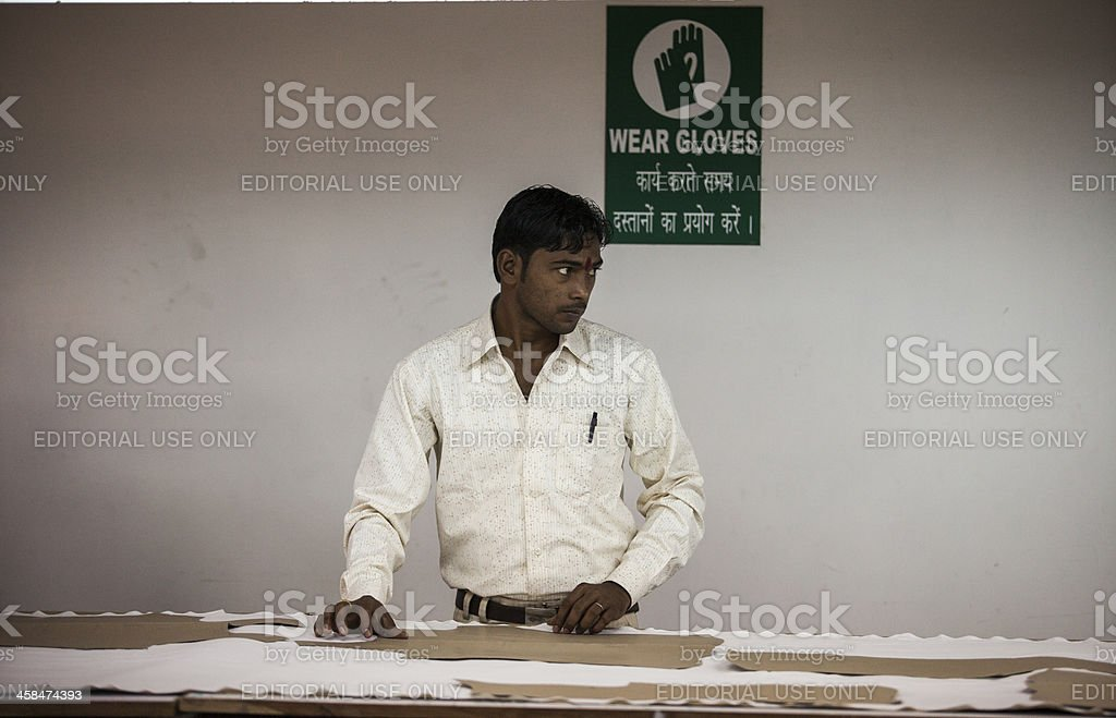 Indian Tailor cuts clothes stock photo