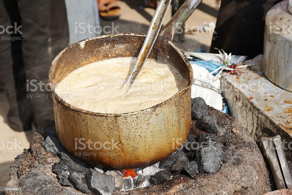 Indian tea with milk boiling on open fire royalty-free stock photo