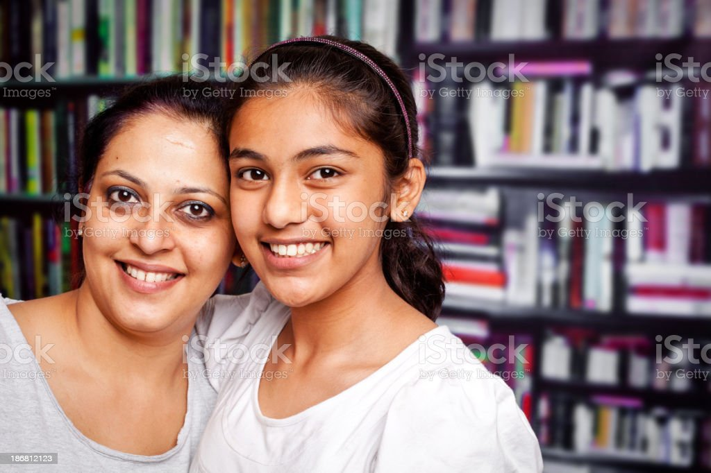Indian Teenager Girl Daughter with her Mother in Library stock photo