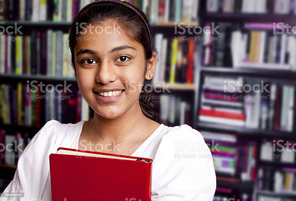 Indian Teenager Girl in a Library with Bookshelf royalty-free stock photo