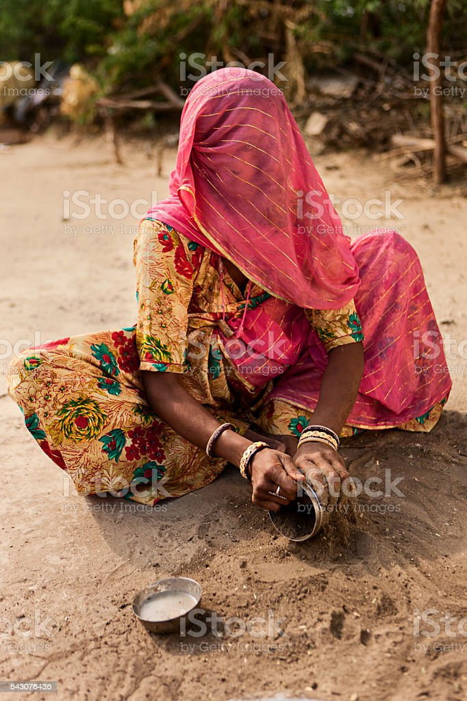 Indian tribal woman washing dishes with sand. Rajasthan, Thar desert stock photo