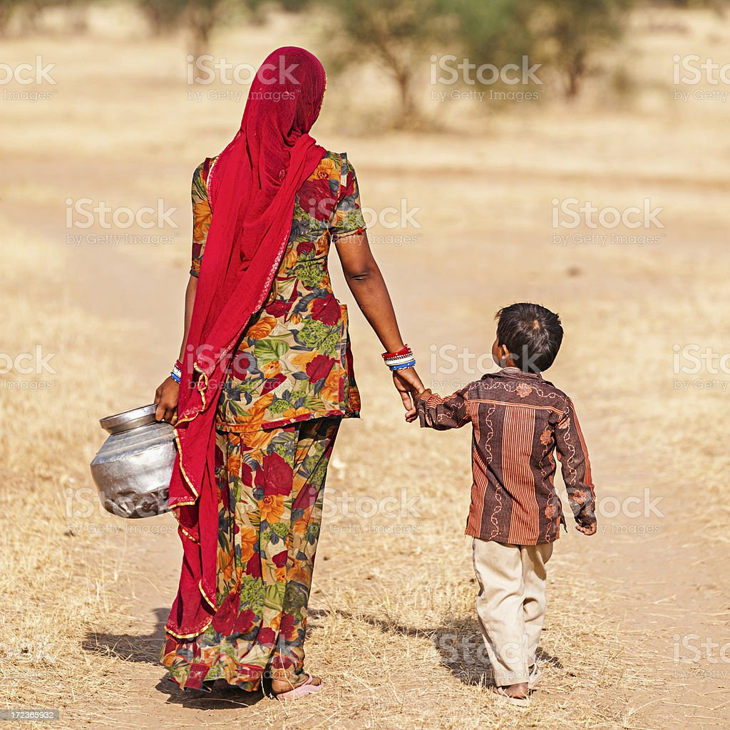 Indian woman carrying water from the well, Rajasthan stock photo