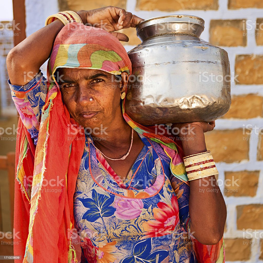 Indian woman carrying water from well stock photo