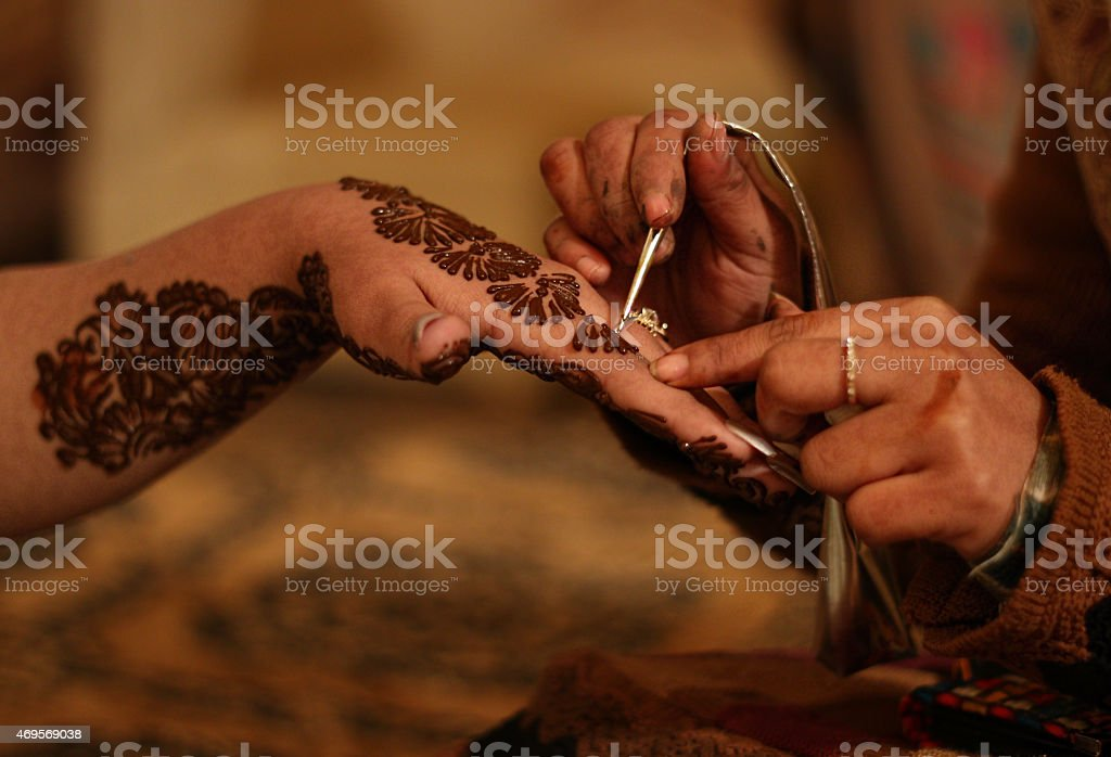 Indian woman getting henna tattoo on her hand stock photo