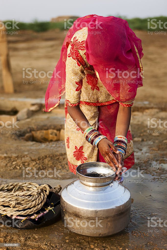 Indian woman getting water from the well, Rajasthan royalty-free stock photo