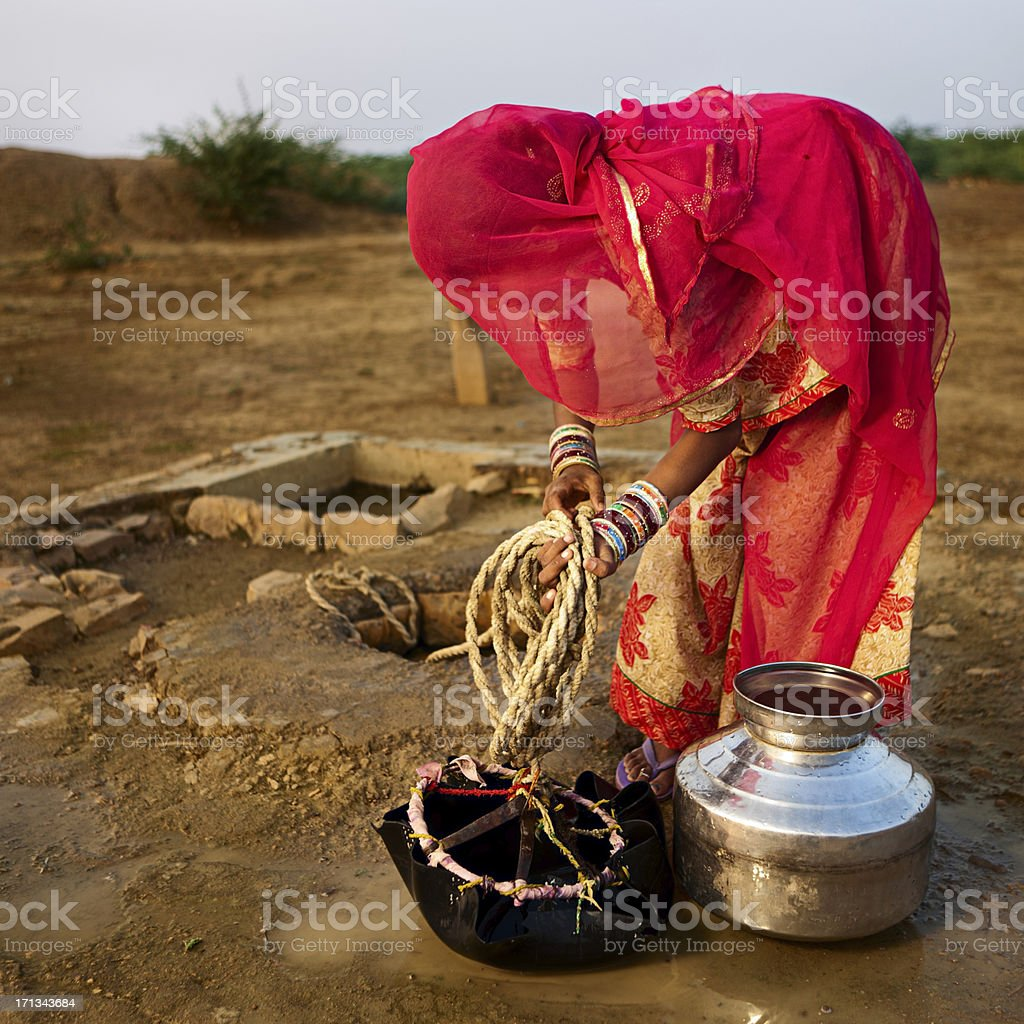 Indian woman getting water from the well. Rajasthan, Thar desert royalty-free stock photo