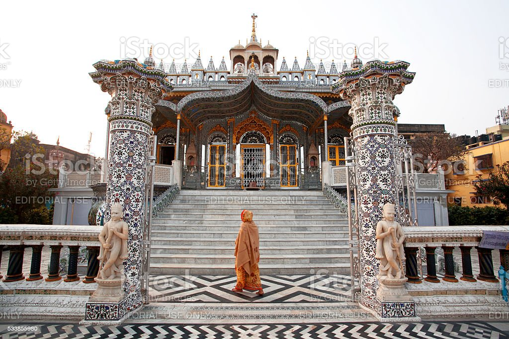 Indian woman goes in front of temple stock photo