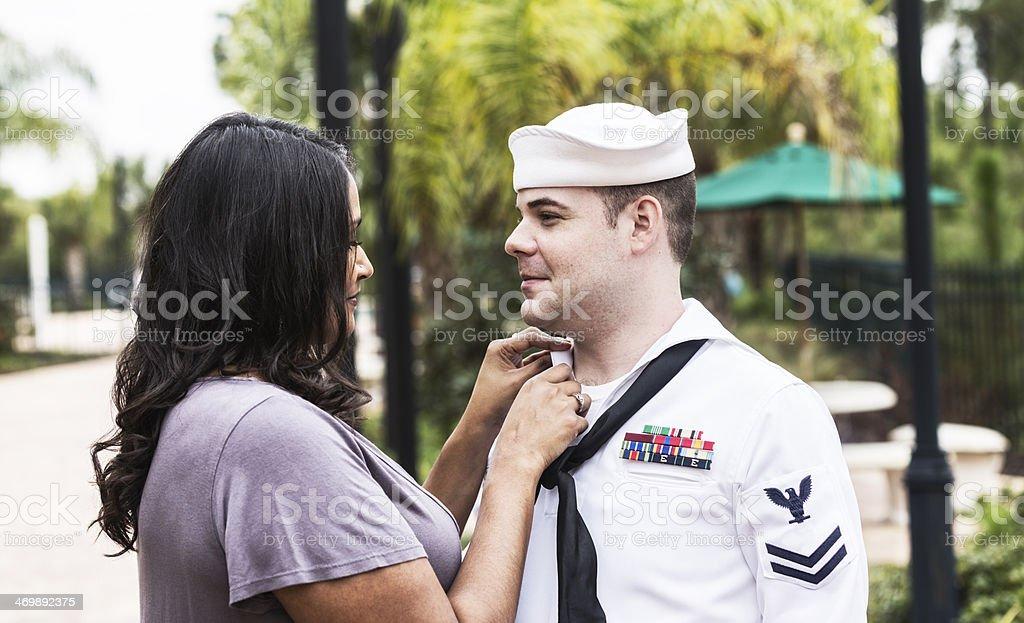 Indian Woman Helping Sailor Husband With Uniform stock photo