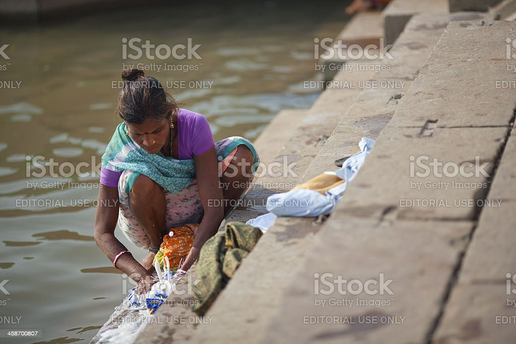 Indian woman in sari washing clothes by the river Ganges stock photo