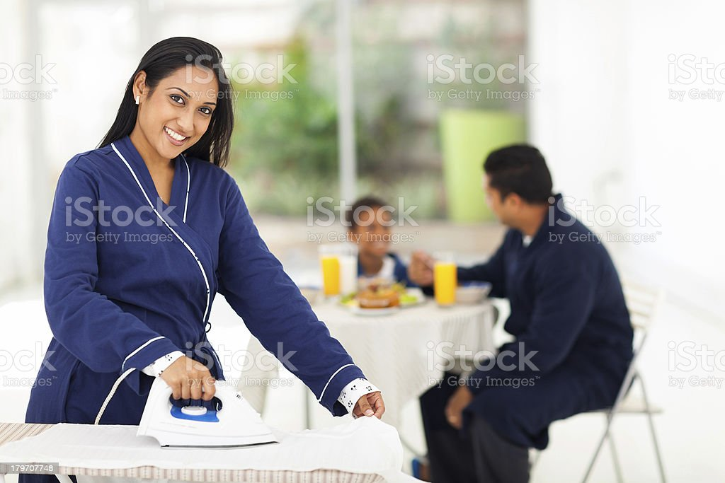 indian woman ironing while husband and son having breakfast royalty-free stock photo