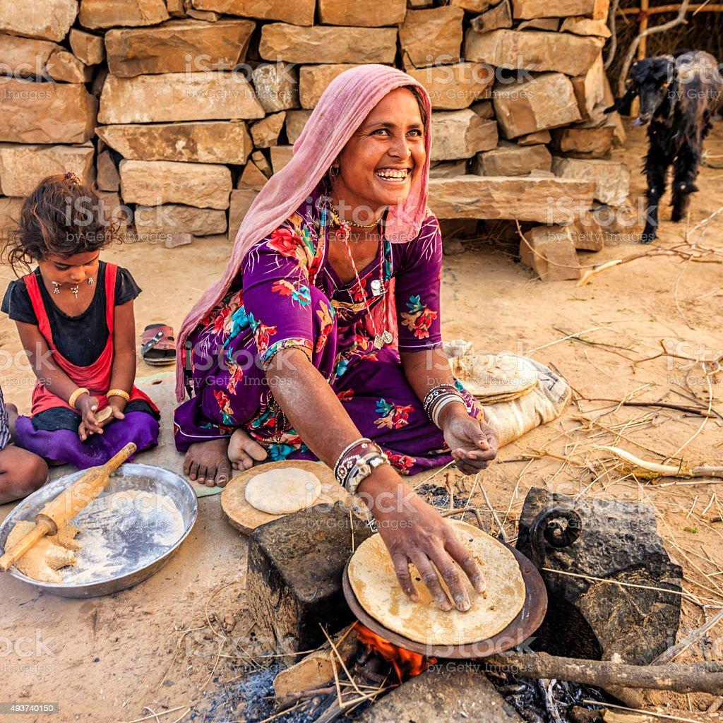 Indian woman preparing food - chapatti, flat bread, desert village stock photo