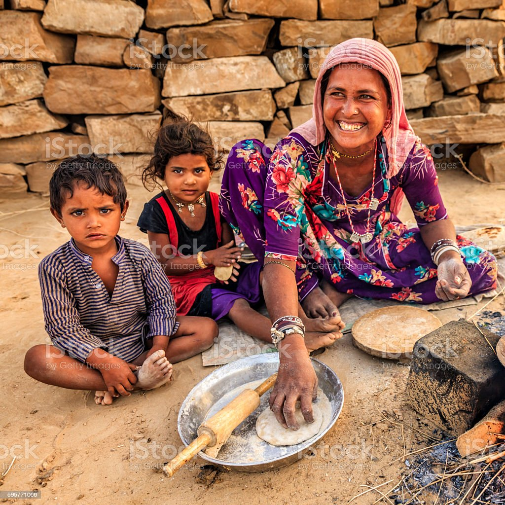 Indian woman preparing food - chapatti, flat bread, desert village stock photo
